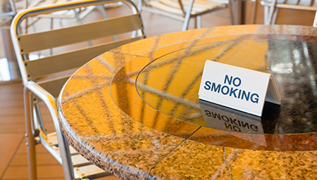 Cafébord utomhus med skylt No smoking. Foto: Colourbox.