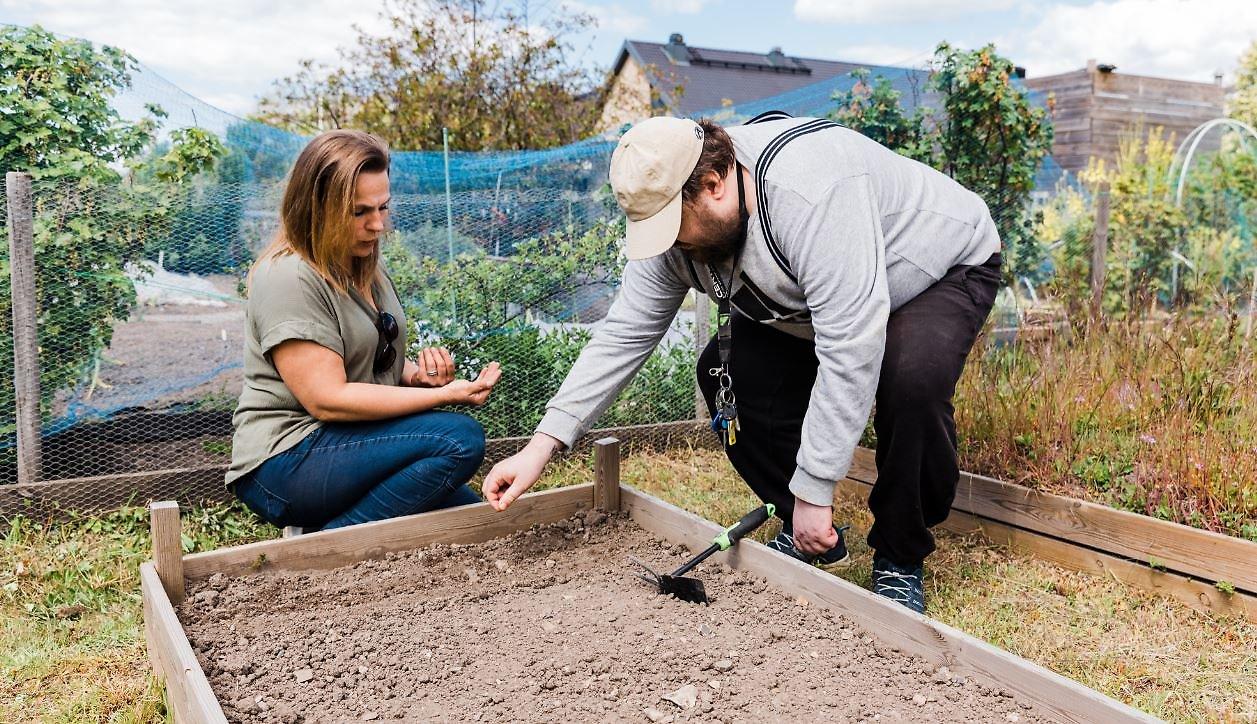 Susanne och Casper sätter fröer i jorden.