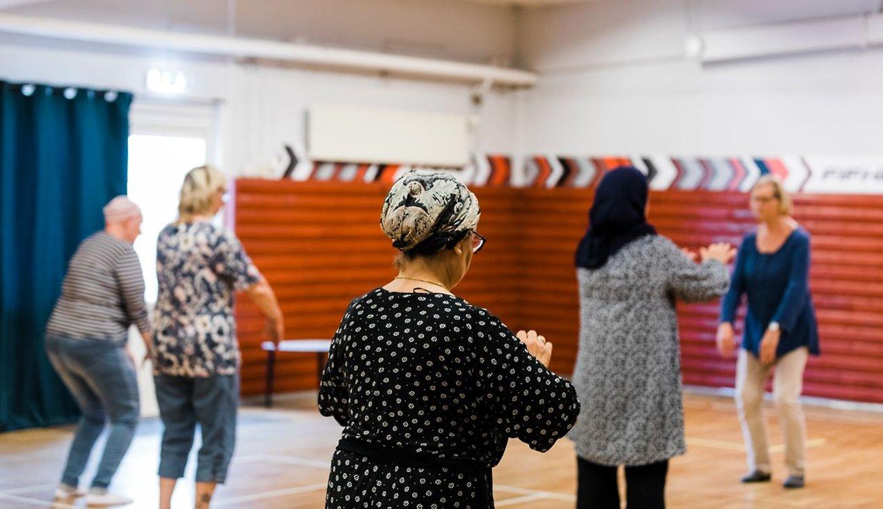 Ett träningspass i basal kroppskännedom. Fem personer står i en gympasal och håller fram armarna.
