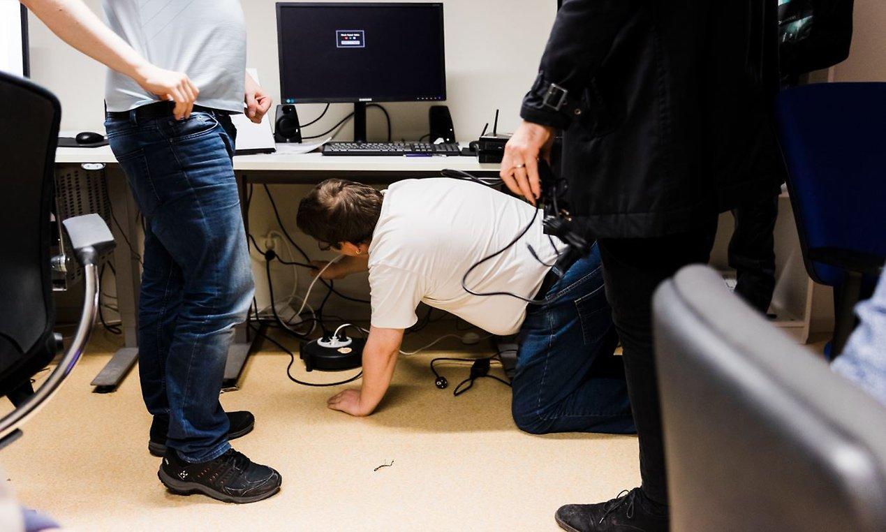 En av Terabytes deltagare kryper på golvet för att se vart sladdar från en dator leder.
