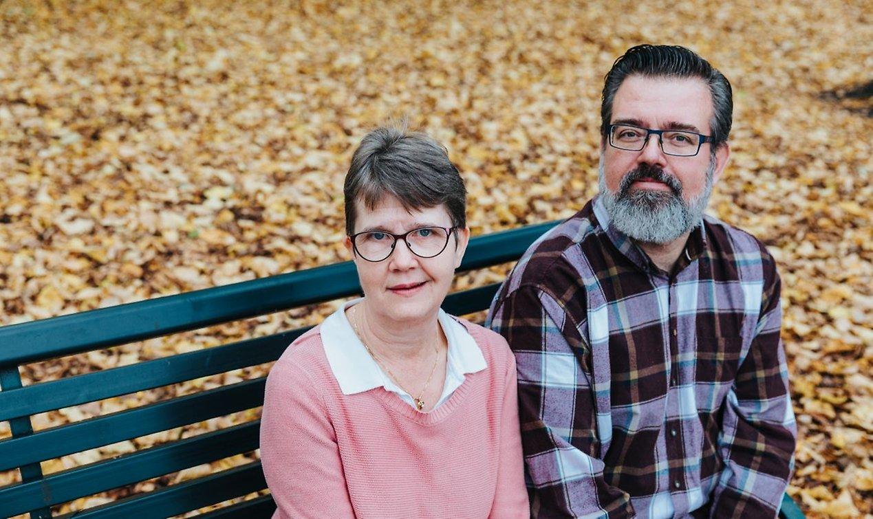 Kristina och Tom sitter bredvid varandra på en bänk bland höstlöv.