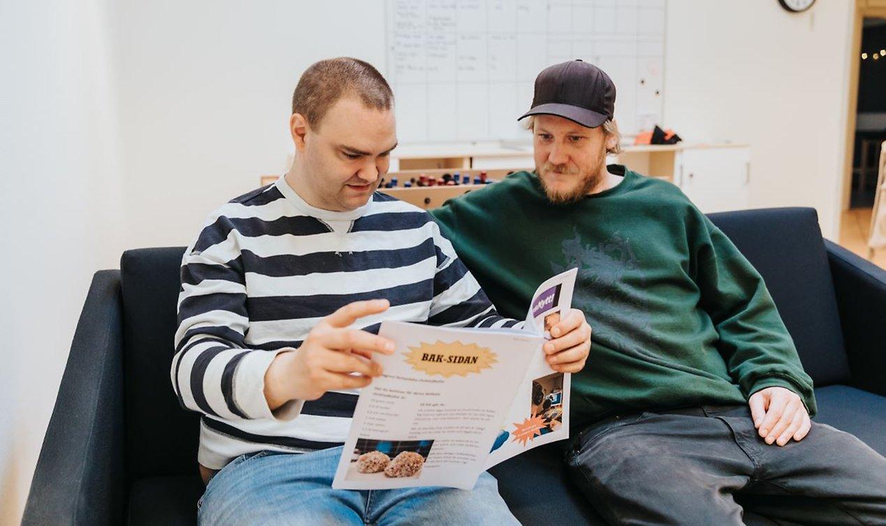 John och Loa bläddrar i ett nummer av PildammsNytt