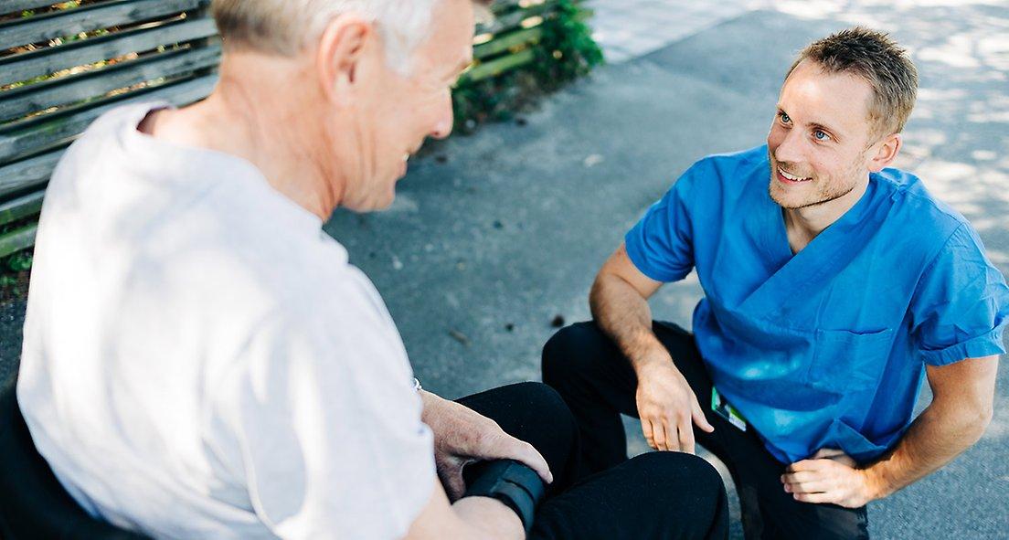 Man i rullstol tittar ner mot en yngre man som hukar.