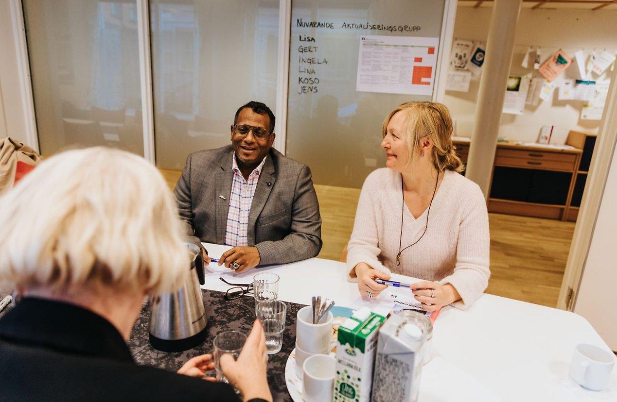 Abdulfatah och Judit sitter vid ett bord, pratar och ler.